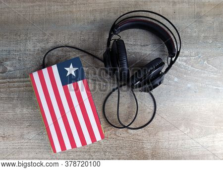 Headphones And Book. The Book Has A Cover In The Form Of Liberia Flag. Concept Audiobooks. Learning