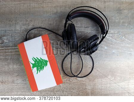Headphones And Book. The Book Has A Cover In The Form Of Lebanon Flag. Concept Audiobooks. Learning