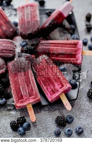 Homemade fresh frozen blueberry and blackberry popsicles on black plate with ice sitting on stone table with fresh berries on side. Top view, flat lay