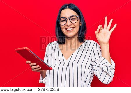 Young beautiful latin woman holding touchpad doing ok sign with fingers, smiling friendly gesturing excellent symbol