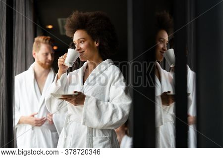 Beautiful Black Woman In Bath Robe Is Holding A Cup And Smiling While Resting At Hotel, Spa