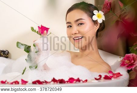 Relaxing Beautiful Asian Woman Pampering Her Body In Water In A Spa Bathtub With White Foam Bubble O