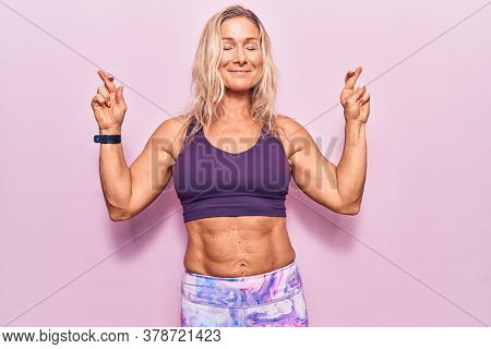 Middle age caucasian blonde woman wearing sportswear over pink background gesturing finger crossed smiling with hope and eyes closed. luck and superstitious concept.