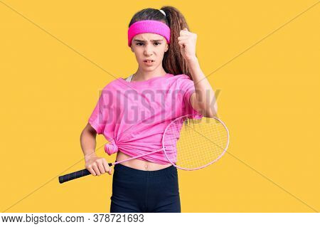 Cute hispanic child girl holding badminton racket annoyed and frustrated shouting with anger, yelling crazy with anger and hand raised
