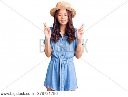 Young beautiful chinese girl wearing summer hat gesturing finger crossed smiling with hope and eyes closed. luck and superstitious concept.
