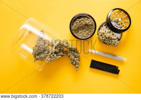 Joint Weed. The Pot Leaves On Buds. Yellow Background. Cannabis Weed Bud And Grinder.
