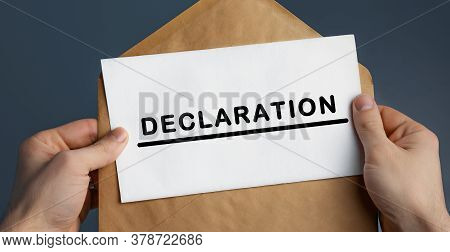 Male Hands Holding Craft Envelope With Text Declaration On Blue Background