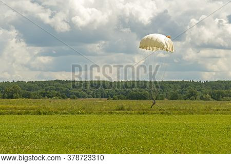 Skydiver Paratrooper In Parachute Dome Before Touchdown In The Set Area To Land Situated In The Fiel
