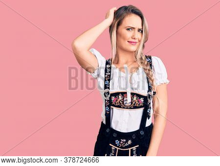 Young beautiful blonde woman wearing oktoberfest dress confuse and wonder about question. uncertain with doubt, thinking with hand on head. pensive concept.