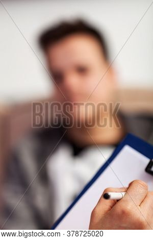 Counselor, psychiatrist or doctor taking notes on teenager young boy or writing a receipt - shallow depth, focus on hand