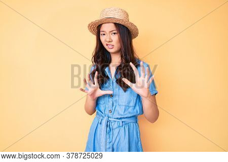 Young beautiful chinese girl wearing summer hat disgusted expression, displeased and fearful doing disgust face because aversion reaction. with hands raised