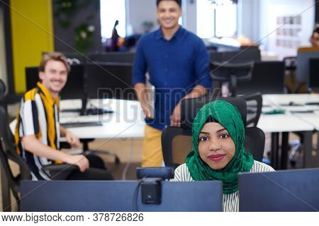 Multiethnic startup business team Arabian woman wearing a hijab on meeting in modern open plan office interior brainstorming, working on laptop and desktop computer