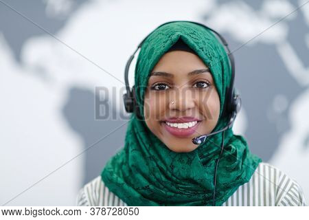 African muslim female with green hijab scarf customer representative business woman with phone headset helping and supporting online with customer in modern call centre