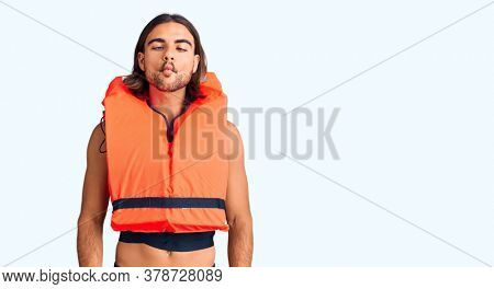 Young handsome man wearing nautical lifejacket making fish face with lips, crazy and comical gesture. funny expression.