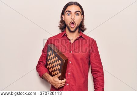 Young handsome man holding chess scared and amazed with open mouth for surprise, disbelief face