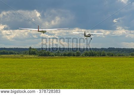 A Plane Towing A Glider Take Off From The Ground Of The Airfield, Covered With Cut Grass On A Backgr