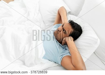 people, bedtime and rest concept - annoyed indian man lying in bed at home and covering ears