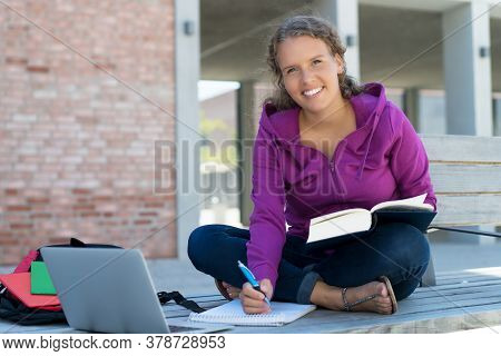 Blond German Female Student Learning With Book And Computer In Front Of School Building Outdoor In S
