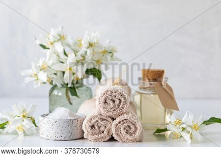 Spa Concept Of Jasmine Oil, With Bath Salt And Flowers On A White Background. Spa And Wellness Still
