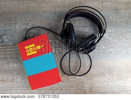 Headphones And Book. The Book Has A Cover In The Form Of Mongolia Flag. Concept Audiobooks. Learning