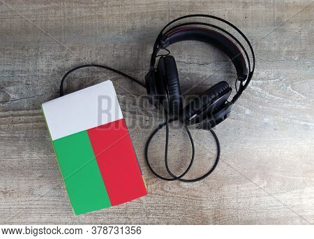 Headphones And Book. The Book Has A Cover In The Form Of Madagascar Flag. Concept Audiobooks. Learni