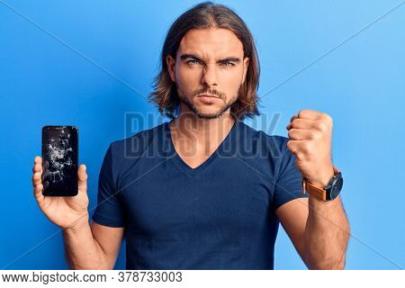 Young handsome man holding broken smartphone showing cracked screen annoyed and frustrated shouting with anger, yelling crazy with anger and hand raised