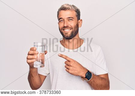 Handsome blond man with beard drinking glass of water to refreshment over white background smiling happy pointing with hand and finger