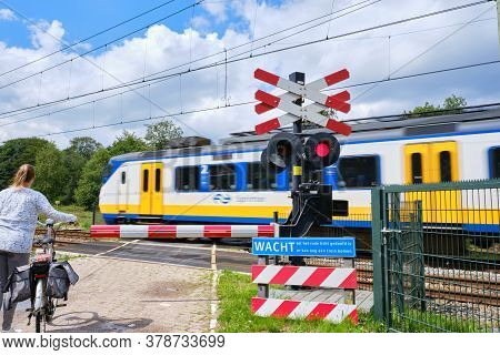 Bennekom-netherlands, Juli 11, 2020:railway Crossing With Barriers And Blinking Red Lights And Unsha