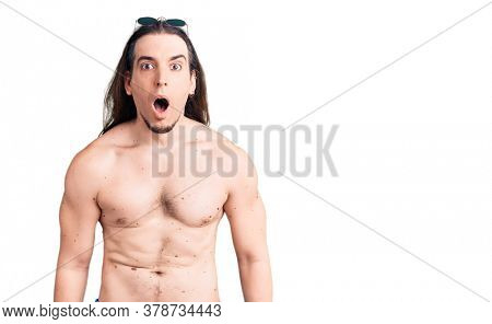 Young adult man with long hair wearing swimwear shirtless scared and amazed with open mouth for surprise, disbelief face