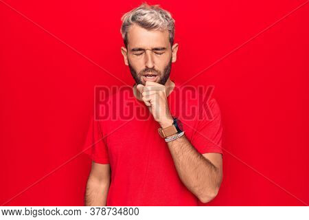 Young handsome blond man wearing casual red t-shirt standing over isolated red background feeling unwell and coughing as symptom for cold or bronchitis. Health care concept.