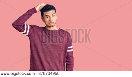 Hispanic handsome young man wearing casual clothes confuse and wonder about question. uncertain with doubt, thinking with hand on head. pensive concept.