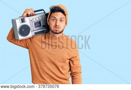Handsome latin american young man holding boombox, listening to music puffing cheeks with funny face. mouth inflated with air, crazy expression.