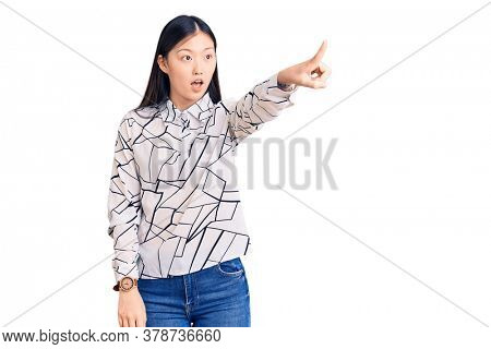 Young beautiful chinese woman wearing casual shirt pointing with finger surprised ahead, open mouth amazed expression, something on the front