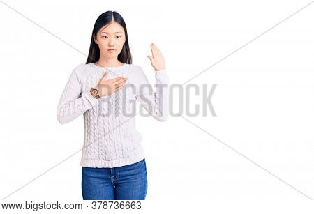 Young beautiful chinese woman wearing casual sweater swearing with hand on chest and open palm, making a loyalty promise oath