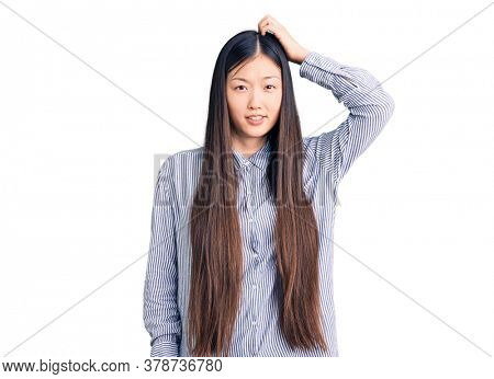 Young beautiful chinese woman wearing casual shirt confuse and wonder about question. uncertain with doubt, thinking with hand on head. pensive concept.