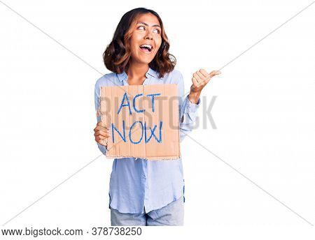 Young beautiful mixed race woman holding act now banner pointing thumb up to the side smiling happy with open mouth
