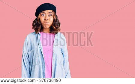 Young beautiful mixed race woman wearing french look with beret puffing cheeks with funny face. mouth inflated with air, crazy expression.