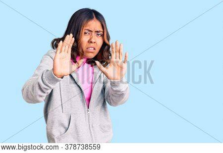 Young beautiful mixed race woman wearing casual sporty clothes disgusted expression, displeased and fearful doing disgust face because aversion reaction. with hands raised
