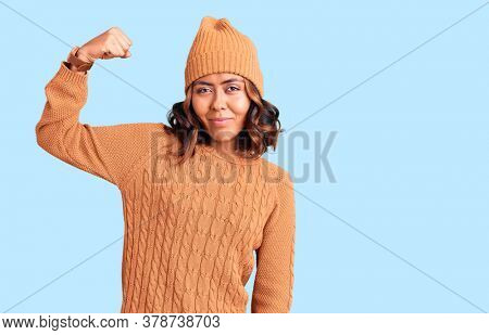 Young beautiful mixed race woman wearing wool sweater and winter hat strong person showing arm muscle, confident and proud of power