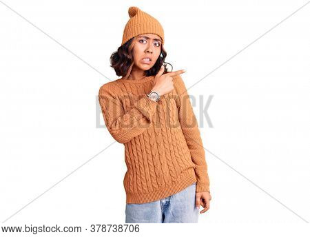 Young beautiful mixed race woman wearing wool sweater and winter hat pointing aside worried and nervous with forefinger, concerned and surprised expression