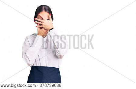 Beautiful brunette young woman wearing professional waitress apron covering eyes and mouth with hands, surprised and shocked. hiding emotion