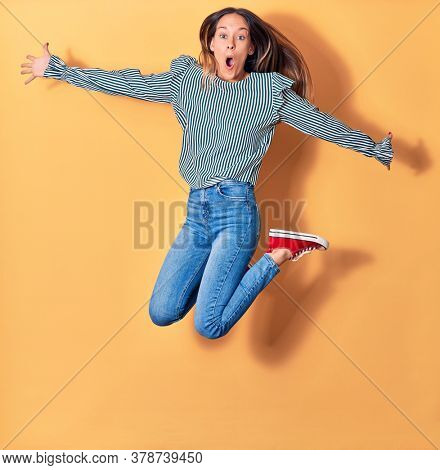 Young beautiful caucasian woman wearing casual clothes surprised with open mouth Jumping with smile on face and arms opened over isolated yellow background