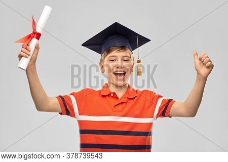 school, education and graduation concept - portrait of happy smiling graduate student boy in bachelor hat or mortarboard with diploma celebrating success over grey background