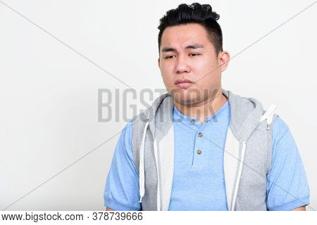 Portrait Of Stressed Young Overweight Asian Man Thinking