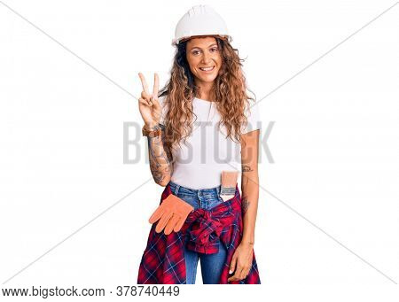 Young hispanic woman with tattoo wearing hardhat and builder clothes showing and pointing up with fingers number two while smiling confident and happy.