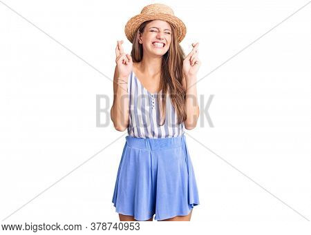 Young beautiful blonde woman wearing summer hat gesturing finger crossed smiling with hope and eyes closed. luck and superstitious concept.