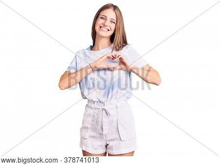 Young beautiful blonde woman wearing tye die tshirt smiling in love showing heart symbol and shape with hands. romantic concept.