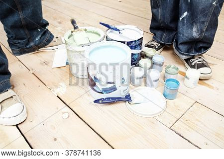 Close up of people and opened paint tins and brushes
