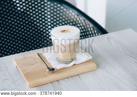 Latte Or Cappuccino In A Glass Cup On A Wooden Tray. Morning Coffee With Foam On A Wooden Table