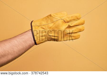 Hand of caucasian young man with gardener glove over isolated yellow background stretching and reaching with open hand for handshake, showing back of the hand